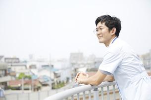 屋上で遠くを見る男性の看護師の写真素材 [FYI04602844]