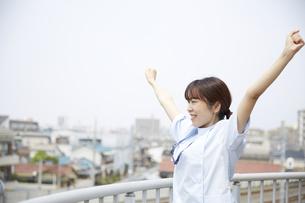 屋上で伸びをする女性の看護師の写真素材 [FYI04602846]