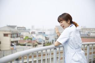 屋上で手を振る女性の看護師の写真素材 [FYI04602847]