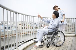 屋上で車椅子の患者と話す女性の看護師の写真素材 [FYI04602848]