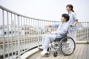 屋上で話す車椅子の患者と女性の看護師の写真素材 [FYI04602849]