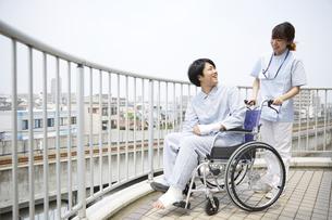 屋上で笑顔で話す車椅子の患者と女性の看護師の写真素材 [FYI04602850]