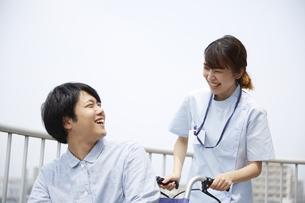 屋上で笑顔で話す車椅子の患者と女性の看護師の写真素材 [FYI04602851]