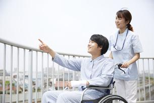 屋上で笑顔で話す車椅子の患者と女性の看護師の写真素材 [FYI04602852]
