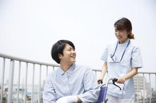 屋上で笑顔で話す車椅子の患者と女性の看護師の写真素材 [FYI04602853]