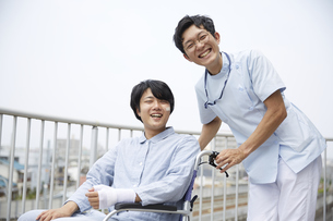 笑顔でカメラ目線の看護師と車椅子の患者の写真素材 [FYI04602855]