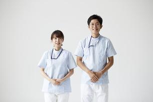 手を組む男女の看護師と白い背景の写真素材 [FYI04602876]