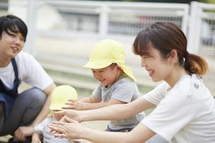 砂場で遊ぶ保育士と子供達の写真素材 [FYI04602913]