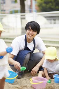 砂場で遊ぶ保育士と子供達の写真素材 [FYI04602914]