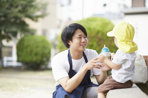 公園で休憩をする子供と保育士の写真素材 [FYI04602923]