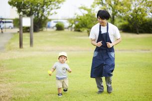 芝生を駆ける子供と保育士の写真素材 [FYI04602925]