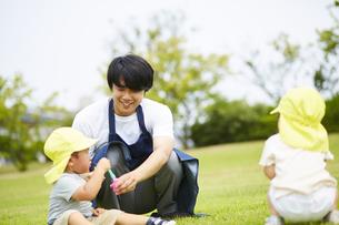 公園で遊ぶ子供達と笑顔の保育士の写真素材 [FYI04602931]
