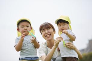 シャボン玉で遊ぶ子供達と笑顔の保育士の写真素材 [FYI04602937]