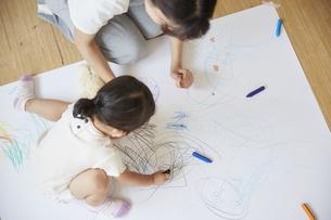 床でお絵描きをする保育士と女の子の写真素材 [FYI04602954]