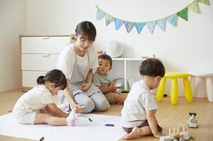 床でお絵描きをする保育士と子供達の様子の写真素材 [FYI04602956]