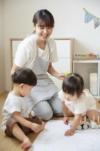 床でお絵描きをする保育士と子供達の様子の写真素材 [FYI04602958]