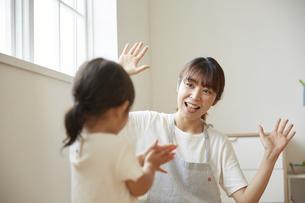 女の子と一緒にダンスをする保育士の写真素材 [FYI04602962]