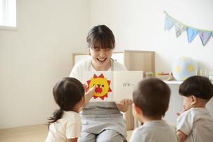 子供達に読み聞かせをする保育士の写真素材 [FYI04602964]