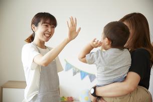 帰宅する子供に手を振る保育士の写真素材 [FYI04602972]