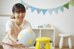 笑顔でボールを差し出す保育士の写真素材 [FYI04602985]