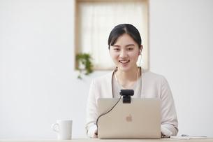 パソコンの前で仕事をする若い女性の写真素材 [FYI04603270]