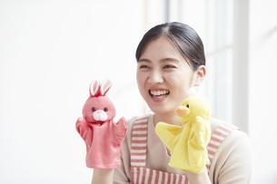 人形を持ち子供をあやすエプロンをした若い女性の写真素材 [FYI04603271]