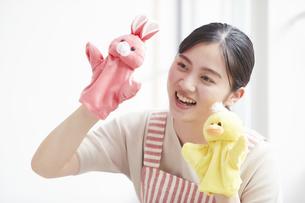 人形を持ち子供をあやすエプロンをした若い女性の写真素材 [FYI04603274]