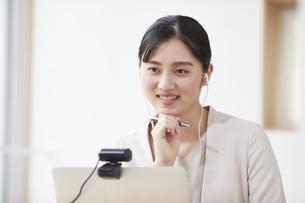パソコンの前で仕事をする若い女性の写真素材 [FYI04603278]