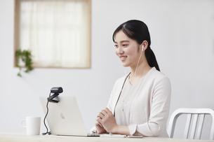 パソコンの前で仕事をする若い女性の写真素材 [FYI04603282]