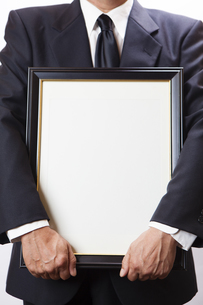 遺影を持つ喪主の男性の写真素材 [FYI04603552]