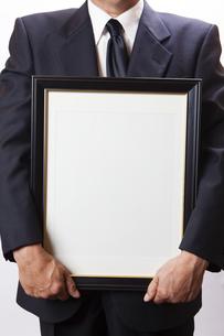 遺影を持つ喪主の男性の写真素材 [FYI04603553]