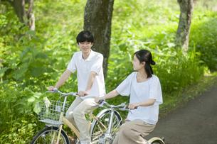 遊歩道で自転車に乗るカップルの写真素材 [FYI04603558]