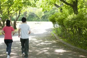 遊歩道でランニングするカップルの後ろ姿の写真素材 [FYI04603561]