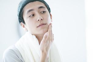 顎に手をあてる若い男性の写真素材 [FYI04603571]