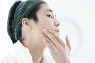 顎に手をあてる若い男性の写真素材 [FYI04603572]