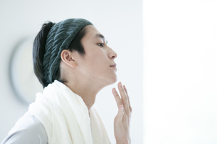 顎に手をあてる若い男性の写真素材 [FYI04603573]