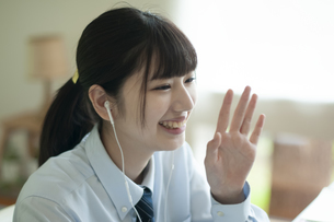 イヤホンをつけ手を振る女子学生の写真素材 [FYI04603791]
