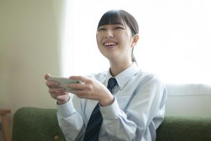 スマホを持ちながら見上げる女子学生の写真素材 [FYI04603802]
