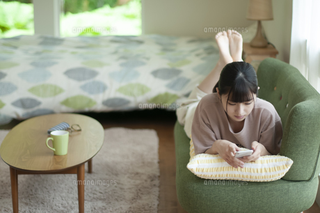 ソファーに寝そべりスマホを見る女子の写真素材 [FYI04603811]