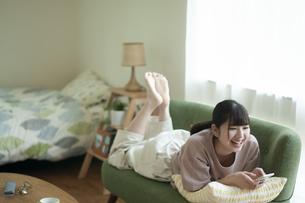 ソファーに寝そべりスマホを見る女子の写真素材 [FYI04603813]