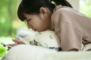 ベットに寝そべりスマホを見る女子の写真素材 [FYI04603821]