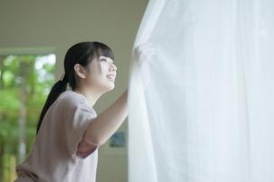 カーテンを開けて外を見る女性の写真素材 [FYI04603852]