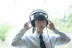 ヘッドホンで音楽を聴く女子学生の写真素材 [FYI04603880]