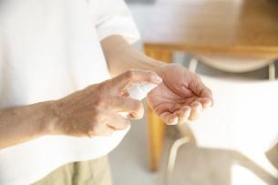 アルコール消毒をするミドルの女性の手元の写真素材 [FYI04603947]