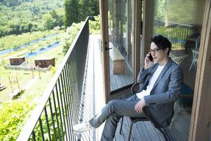 バルコニーで電話をするビジネスマンの写真素材 [FYI04604071]