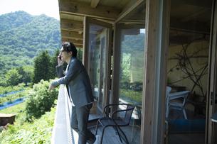 バルコニーで電話をするビジネスマンの写真素材 [FYI04604074]