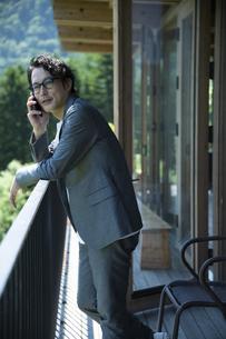 バルコニーで電話をするビジネスマンの写真素材 [FYI04604076]