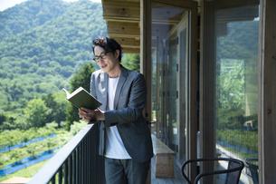 バルコニーで読書をするビジネスマンの写真素材 [FYI04604077]