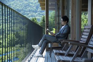 バルコニーで読書をするビジネスマンの写真素材 [FYI04604081]