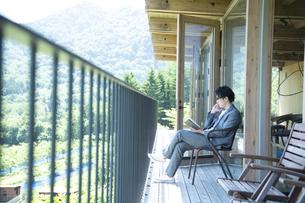バルコニーで読書をするビジネスマンの写真素材 [FYI04604084]
